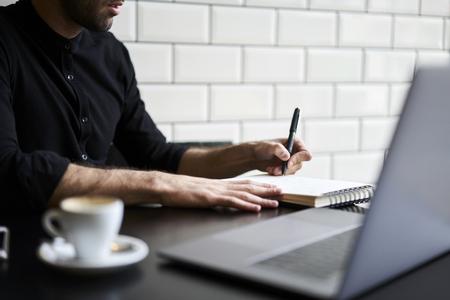 인터넷 소스를 사용 하여 연구하는 숙제를 준비하는 캐주얼에서 매력적인 학생의 잘린 된 이미지. 실내에 앉아 잡지에 논문을 쓰는 전문 저널리스트