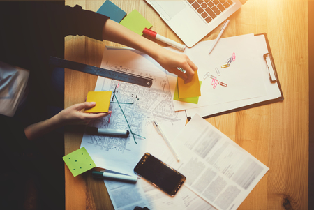 merkt op en wijst naar het creëren van een constructie-indeling met behulp van briefpapier voor het meten en moderne digitale apparaten die op een desktop staan en zijn verbonden met wifi