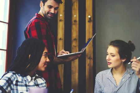 Voor publicatie in online nummer met mannelijke redacteur, jonge collega's die ideeën delen en werken in een vriendelijke sfeer terwijl ze binnenshuis op kantoor zijn Stockfoto