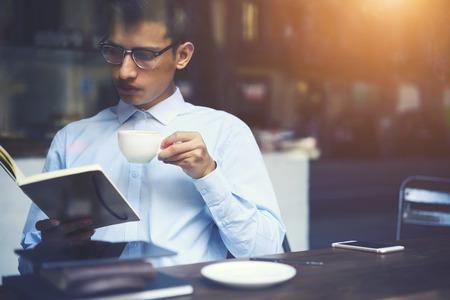 커피 숍에 앉아 쉬는 동안. 카페테리아에서 논픽션 문학으로 자유 시간을 보내는 안경을 쓰고있는 청년