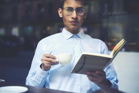 실내 식당에서 자유 시간 동안 흥미로운 탐정 베스트셀러를 읽는 동안. 독서 책에 시간을 보내고 안경에 힙 스 남자
