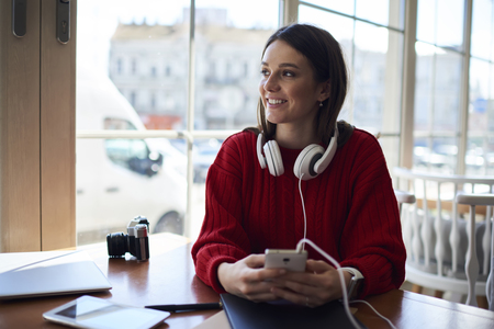 Searching favorite songs online via modern smartphone wear headphones, attractive female student using modern technology gadgets for making research