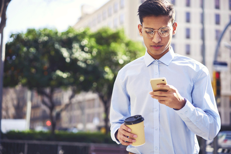 smart teenager installing innovative software on digital smartphone with coffee take away and using free high 4G internet walking outdoors Stock Photo