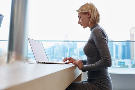 Attractive good looking blonde female freelancer working online with marketing project sitting in coworking space, young businesswoman making distant work using laptop computer while sitting in office Stock Photo