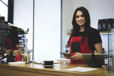 Grazioso giovane barista femminile che ordina per la produzione utilizzando l'applicazione su tavoletta collegata a Internet wireless in caffetteria, professionale cameriera fare il trasferimento di denaro per l'acquisto