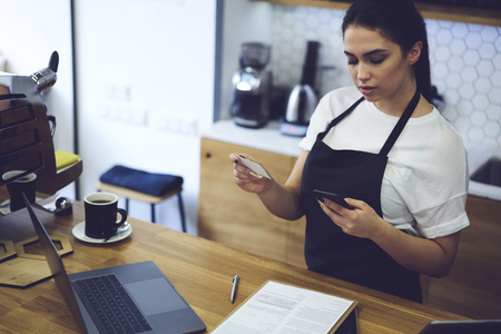 Female administrative manager dial contact information number on cellphone of product supplier for her coffee shop. Young woman entrepreneur of restaurant business calling to delivery service in city