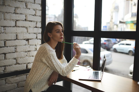 Young female journalist thoughtful thinking about new ideas and inspiring for write interesting article for fashion magazine.Gorgeous woman wondering about thoughts of creating presentation Stok Fotoğraf
