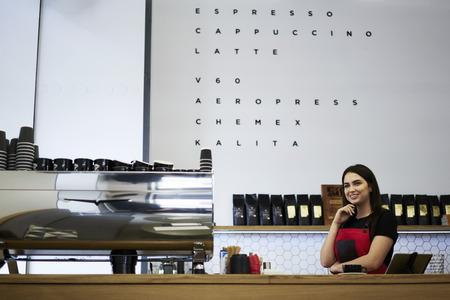 Allegro giovane barista femminile godendo di tempo libero sul lavoro in piedi vicino al bar con macchina da caffè, affascinante cameriera guardando via in attesa del primo cliente di caffetteria pronto a fare ordinazione