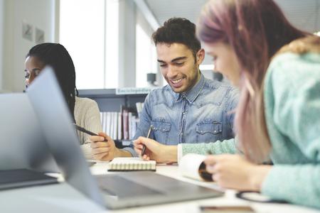 in universiteitsbibliotheek, bekwame groep journalisten die publicatie creëren die details bespreken gebruikend laptop computer en wifiverbinding Stockfoto