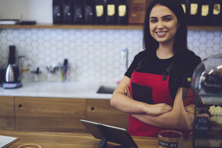 Attractive female businesswoman barista in stylish uniform standing near working place ready to working hard in morning, waitress in good mood greeting clients with nice smile offering coffee drinks