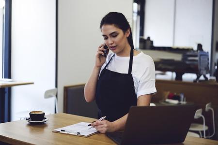 Cameriera attraente parla sullo smartphone e rende i prodotti di controllo al caffè all'interno. Femmina dipendente di caffè presa ordine dal cliente sul telefono cellulare in piedi al tavolo con computer portatile moderno
