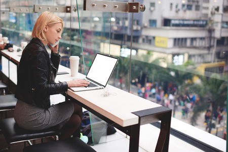 Confident attractive blonde young business woman having phone conversation with colleague while making distant work using modern laptop computer with mock up screen 版權商用圖片
