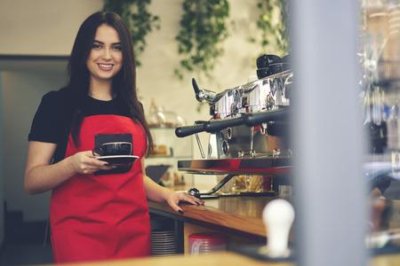 Ritratto di mezza lunghezza di attraente barista femminile fare americano utilizzando macchina da caffè professionale in caffetteria, sorridente attraente cameriera di sesso femminile godendo di processo di lavorazione cappuccino tazza