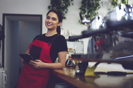 Cheerful waitress in uniform resting during break on work standing near bar with modern touchpad using wifi connection for chatting with colleagues, portrait of female barista smiling to the camera