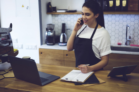 Smiling waitress talking on modern mobile phone with customer and informing about products of cafeteria.Barista taking order on cellular using paper and pen for records standing at counter with laptop