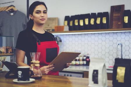 Ritratto di attraente barista femminile che lavora in caffetteria in buon umore in attesa di ordinare vestito in grembiule, bella cameriera avendo giorno lavorativo in caffè con dispositivo digitale touch pad
