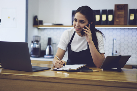 Caucasian student working waitress in coffee shop. Beautiful female employee talking with customers on work telephone and making taking order noting details sitting at wooden table with modern gadgets