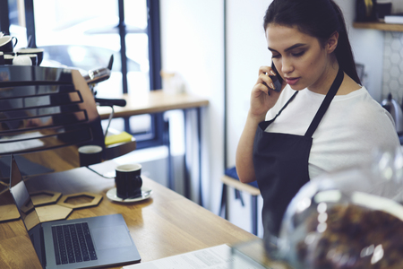 Young charming barista communicating with manager during break on digital mobile phone. Female young employee of coffee shop talking with boss on cellular and reporting him about income of working day