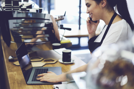 Cropped image of beautiful barista searching interesting idea making aroma coffee in internet while talking with friend on telephone during break. Waitress calling to bank to check money payment Archivio Fotografico