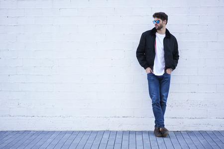 Full length portrait of young handsome model dressed in casual outfit and style sun glasses standing on street and looking away on copy space area