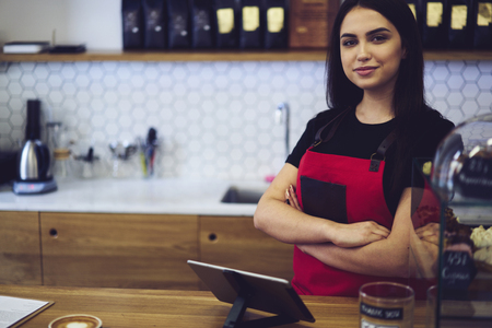 Portrait of confident administrative manager feeling confident during working process, professional female barista waiting for order to make aroma coffee for client standing near modern equipment
