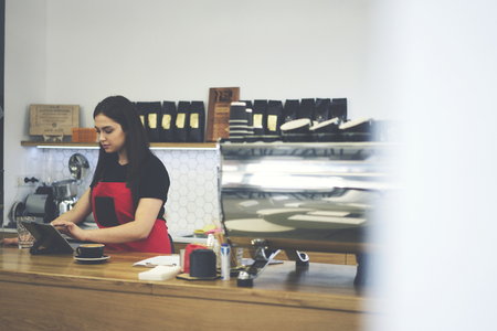 Professional female cashier in uniform using modern technology and wifi connection  for registration new order counting bills for client, concentrated waitress working hard in contemporary coffee shop