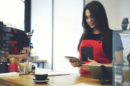 Dirigente amministrativo femminile professionale di coffee shop vestito in banca uniforme tramite touchpad collegato a wifi, cameriera affascinante con applicazione per il conteggio dei redditi da vendita durante il giorno lavorativo