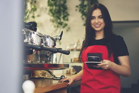 Ritratto di mezza lunghezza di attraente barista femminile vestito in uniforme azienda tazza americana per il cliente, cameriera allegra godendo giorno lavorativo in caffetteria facendo caffè aroma utilizzando attrezzature