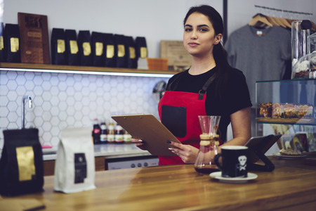Portrait of prosperous successful female administrative manager of coffee shop checking readiness for working day counting products due to invoice, experienced female barista preparing for revision