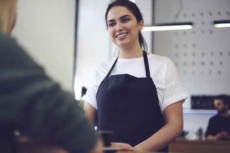 Portrait of charming waitress in good mood communicating with client offering best coffee drinks help customer to make choice, beautiful young cheerful female barista ready for taking ordering Stock Photo