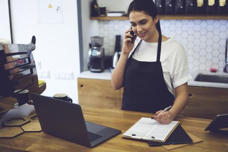 Bellissimo imprenditore qualificato vestito di grembiule nero con la modella in su fare affari di caffè da solo. Sorridente barista in piedi al bar e parlando con il consulente web su ordinazione di cibo per la caffetteria