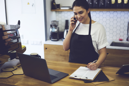 Beautiful skilled entrepreneur dressed in black apron with mock up making coffee business by herself. Smiling barista standing at bar and talking with web consultant about ordering food for cafeteria Archivio Fotografico