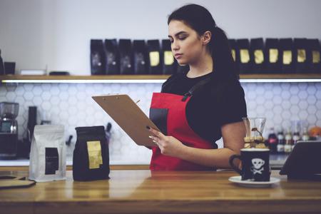Fiducioso gestore amministrativo femminile attraente che effettua revisione controllo quantità di prodotti che contano reddito mensile lavorando con la documentazione durante il lavoro duro