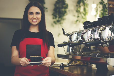 Portrait of young attractive waitress holding americano for customer ordering dressed in brand uniform, professional cute female barista made americano using coffee machine working in cafeteria Archivio Fotografico