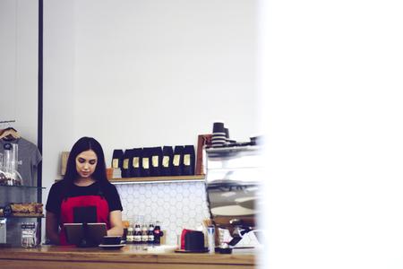 Concentrato serio cameriera rendendo l'ordinazione on-line in caffetteria utilizzando moderni touch pad collegato a wifi, manager amministrativo controllo applicazione per la segnalazione finanziaria e database