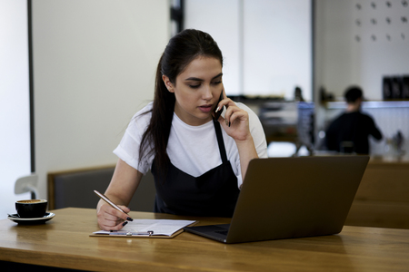 Female owner of modern cafeteria talking on mobile phone with consultant web store for making order of new coffee machine in cafeteria interior while writing