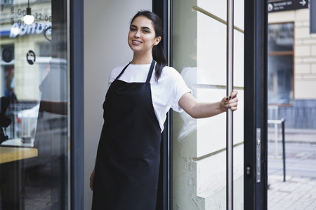 Mezza lunghezza ritratto di cameriera vestita di grembiule nero con spazio di copia per il marchio open store inizio lavoro pronto a servire i visitatori, donna imprenditore barista in piedi all'ingresso del ristorante