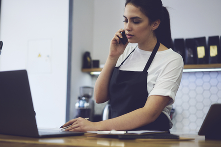 Young female owner calling to bank for checking finance documentation in cafeteria. Beautiful charming barista of coffee shop makes accounting after work and reports to director by mobile phone