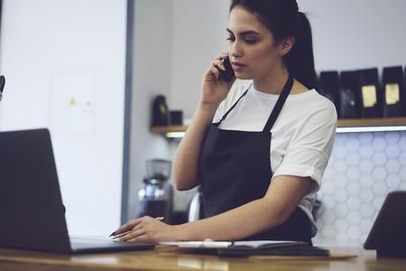 Giovane proprietario femminile che chiama banca per controllare la documentazione finanziaria in caffetteria. Bellissimo affascinante barista di caffetteria rende contabile dopo il lavoro e riferisce al direttore dal cellulare