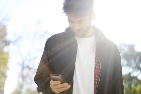 Young bearded hipster guy casual dressed in style look walking outdoors in city using online application on cellphone. Stylish man browsing internet via smartphone standing on street in sunny day Stock Photo