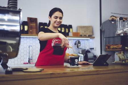 Allegro giovane apprendista femminile che insegna come preparare l'eccellente americano usando strumenti speciali per risparmiare aroma e gusto migliorano le sue capacità, creatore di caffè sorridente fiducioso godendo del processo di lavoro