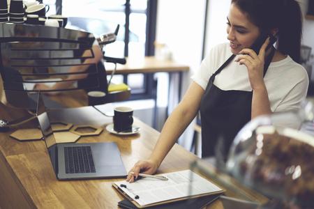 Cassiere femminile con buon umore rendendo rapporto finanziario alla fine durante il giorno lavorativo mentre parla con gli amici smartphone moderno su riunione dopo il caffè in piedi standing