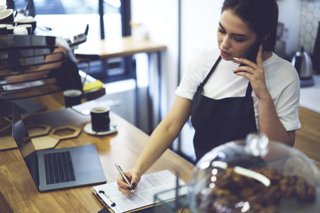 Female owner of coffee shop having phone conversation with banking service consulting about filing financial reports while using laptop to check accountings from database. Restaurant entrepreneur