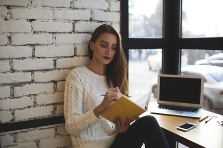 Attractive female entrepreneur verifying financial accounting documentation recorded in notebook.Creative administrative manager checking work action plan written last month in diary sitting in cafe Imagens