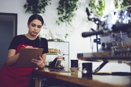Dirigente amministrativo professionale concentrato di caffè che effettua revisioni dopo giorno lavorativo utilizzando la documentazione e la contabilizzazione dei redditi da servizio e vendita