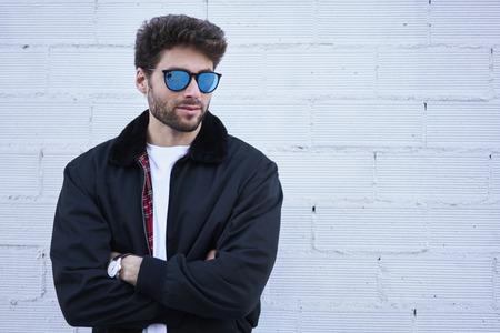 プロモーション春ファッション衣類のコピー領域とウォールストリートの背景にポーズ流行のサングラスの良いスタイリッシュな流行に敏感な男