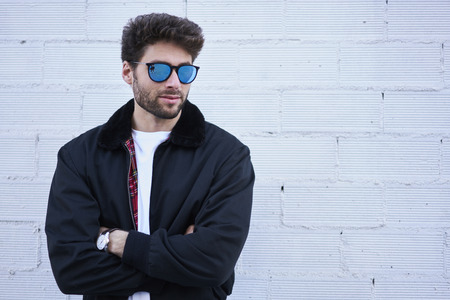 Good looking stylish hipster guy in trendy sunglasses posing on street wall background with copy space area for promotional spring fashion clothing