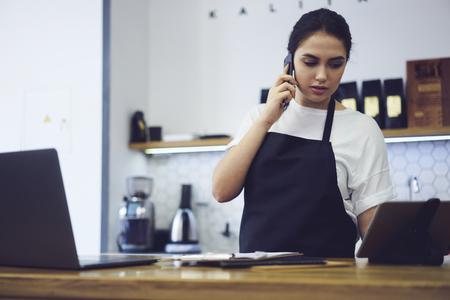 Imprenditore caucasico modello vestito in grembiule con mock up avendo conversazione con i clienti su smartphone durante la finanza accounting conta in piedi al bar con il moderno computer portatile