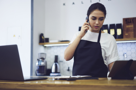 Caucasian model entrepreneur dressed in apron with mock up having conversation with clients on smartphone during making finance accounting standing at bar with modern laptop