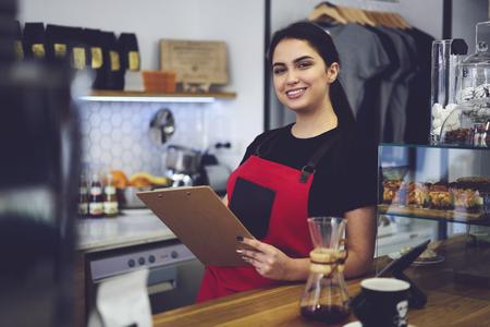 Retrato de un alegre miembro del personal femenino de la cafetería listo para comenzar a trabajar debido al contrato vestido con uniforme de delantal, sonriente gerente administrativo contando los ingresos anuales del servicio y las ventas